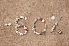 Text 60 por cento na areia feita do shell Fotos de Stock Royalty Free