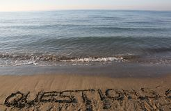 Text QUESTIONS on the sand by the sea royalty free stock photography