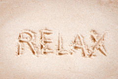 Text Relax writing on sand at the beach Stock Photos