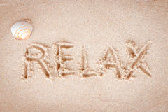 Text Relax writing on sand at the beach Royalty Free Stock Image