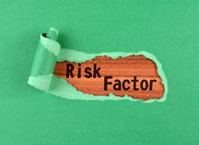 Risk factor word. The text Risk factor appearing behind ripped green paper on wood royalty free stock photography