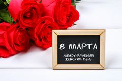 Text in Russian: March 8. Black chalkboard and roses. International Women`s Day. Text in Russian: March 8. Black chalkboard and roses. International Women`s Day Royalty Free Stock Photos