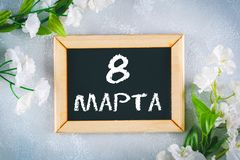 Text in Russian: March 8. Black chalkboard and white flowers. International Women`s Day. Text in Russian: March 8. Black chalkboard and white flowers Royalty Free Stock Images