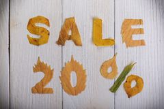 Sale 20 percent. The text `sale, 20 percent` cut from different yellow and orange fallen leaves from the trees and laid on the white wooden boards Royalty Free Stock Photo