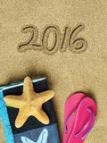 2016 text on sand. And beach accessories Stock Image
