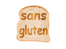Text sans gluten (meaning gluten free in French) toasted on a slice of bread, isolated on white Royalty Free Stock Photography