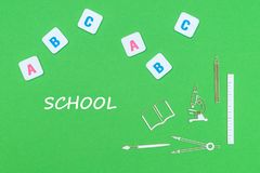 Text school, from above wooden minitures school supplies and abc letters on green background. Concept school, text school, school supplies wooden minitures, abc Royalty Free Stock Image