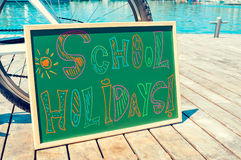 Text school holidays written in a chalkboard Stock Photo