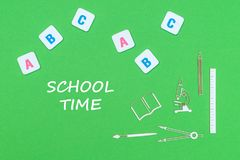 Text school time, from above wooden minitures school supplies and abc letters on green background. Concept school, text school time, school supplies wooden Stock Photography