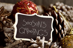 Text seasons greetings, pine cones and baubles Stock Image