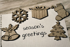 Text seasons greetings and some christmas ornaments. Closeup of a piece of paper with the text text seasons greetings written in it and some christmas ornaments royalty free stock image