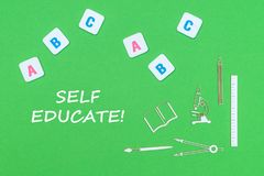 Text self educate, from above wooden minitures school supplies and abc letters on green background. Concept school, text self educate, school supplies wooden stock photography