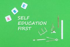 Text self education first, from above wooden minitures school supplies and abc letters on green background. Concept school, text self education first, school Royalty Free Stock Photos
