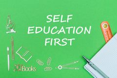 Text self education first, school supplies wooden miniatures, notebook with ruler, pen on green backboard. Concept school, text self education first, school Stock Photography