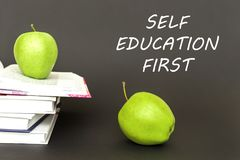 Text self education first, two green apples, open books with concept. Concept back to school, text self education first, two green apples, open books on gray Stock Photos