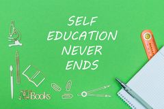 Text self education never ends, school supplies wooden miniatures, notebook with ruler, pen on green backboard. Concept school, text self education never ends Stock Image