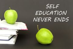 Text self education never ends, two green apples, open books with concept. Concept back to school, text self education never ends, two green apples, open books Stock Image