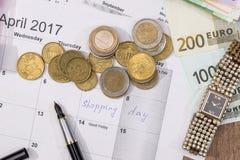 Text shopping day write on calendar with euro. Banknotes, coin, pen Stock Photos