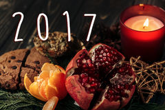 2017 text sign new year number on stylish rustic christmas wallpaper candle and garnet cookies fruits on wooden background. Seasonal greetings for winter royalty free stock images
