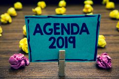 Text sign showing Agenda 2019. Conceptual photo list of activities in order which they are to be taken up Clothespin holding blue. Paper note crumpled papers Royalty Free Stock Image