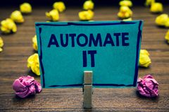 Text sign showing Automate It. Conceptual photo convert process or facility to be operated automatic equipment. Clothespin holding. Blue paper note crumpled royalty free stock images