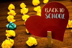 Text sign showing Back To School. Conceptual photo Return to class first day of studies Classroom Arriving Text red heart wood cli. P desk crumbled paper notes stock photo