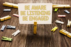 Text sign showing Be Aware Be Listening Be Engaged. Conceptual photo take attention to actions or speakers Clothespin holding whit. E paper note several Royalty Free Stock Images