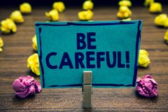 Free Text Sign Showing Be Careful. Conceptual Photo Making Sure Of Avoiding Potential Danger Mishap Or Harm Clothespin Holding Blue Pap Royalty Free Stock Image - 123872796