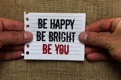 Text sign showing Be Happy Be Bright Be You. Conceptual photo Self-confidence good attitude enjoy cheerful Man holding. Piece notebook paper jute background royalty free stock image