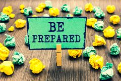 Text sign showing Be Prepared. Conceptual photo make something ready for use or consideration at future Clothespin holding green n. Ote paper crumpled papers stock image