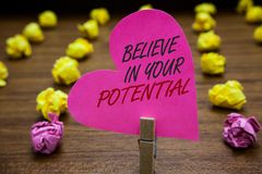 Text sign showing Believe In Your Potential. Conceptual photo Have self-confidence motiavate inspire yourself Paperclip hold pink. Heart with text blurry paper royalty free stock photography