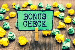 Text sign showing Bonus Check. Conceptual photo something in addition to what is expected or strictly due Clothespin holding green. Note paper crumpled papers stock photo