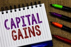 Text sign showing Capital Gains. Conceptual photo Bonds Shares Stocks Profit Income Tax Investment Funds Open spiral notebook page