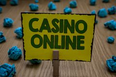 Text sign showing Casino Online. Conceptual photo Computer Poker Game Gamble Royal Bet Lotto High Stakes Clothespin holding yellow. Paper note crumpled papers royalty free stock photography