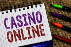 Text sign showing Casino Online. Conceptual photo Computer Poker Game Gamble Royal Bet Lotto High Stakes Open spiral notebook page. Jute background colorful stock photography