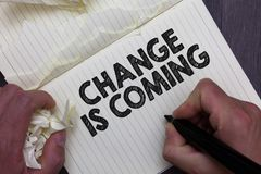 Text sign showing Change Is Coming. Conceptual photo telling someone that future going to be different Man holding marker notebook. Crumpled papers ripped pages stock photography