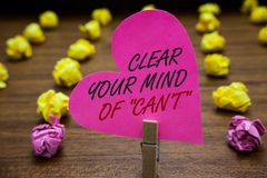 Text sign showing Clear Your Mind Of Can t not. Conceptual photo Have a positive attitude thinking motivation Paperclip hold pink. Heart with text blurry paper Stock Photography