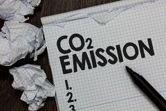 Text sign showing Co2 Emission. Conceptual photo Releasing of greenhouse gases into the atmosphere over time Marker over notebook. Crumpled papers ripped pages stock photo