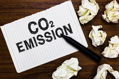Text sign showing Co2 Emission. Conceptual photo Releasing of greenhouse gases into the atmosphere over time Marker over notebook. Crumpled papers ripped pages stock photos