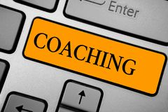 Text sign showing Coaching. Conceptual photo person supports client in achieving specific personal goal Keyboard orange key Intent royalty free stock photo
