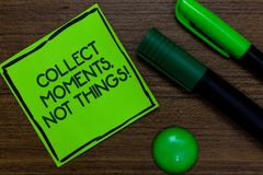 Text sign showing Collect Moments, Not Things. Conceptual photo Happiness philosophy enjoy simple life facts Written on sticky not. E two markers laid on wooden royalty free stock photography