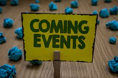 Text sign showing Coming Events. Conceptual photo Happening soon Forthcoming Planned meet Upcoming In the Future. Clothespin holding yellow paper note crumpled stock photography