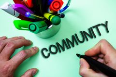 Text sign showing Community. Conceptual photo Neighborhood Association State Affiliation Alliance Unity Group Man holding black ma. Rker white background markers Stock Photo