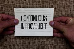 Text sign showing Continuous Improvement. Conceptual photo Ongoing Effort to Advance Never ending changes Man holding. Piece notebook paper jute background stock image
