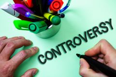Text sign showing Controversy. Conceptual photo Disagreement or Argument about something important to people Man holding black mar. Ker white background markers Royalty Free Stock Images