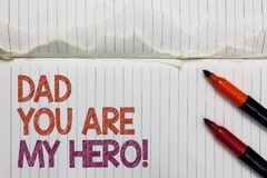Text sign showing Dad You Are My Hero. Conceptual photo Admiration for your father love feelings compliment White torn page writte. N some letters beside laid royalty free stock photos