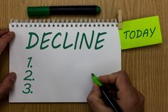 Text sign showing Decline. Conceptual photo Become smaller fewer less Decrease Politely refuse reject say no Man holding. Marker notebook clothespin reminder stock image