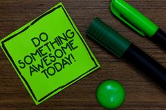 Text sign showing Do Something Awesome Today. Conceptual photo Make an incredible action motivate yourself Written on sticky note. Two markers laid on wooden Stock Photography