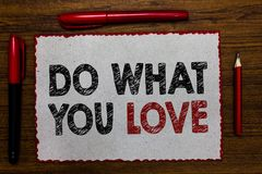 Text sign showing Do What You Love. Conceptual photo Make enjoyable things do activities with motivation Red bordered white page c. Entered some texts wooden royalty free stock image