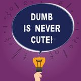 Text sign showing Dumb Is Never Cute. Conceptual photo To be stupid ignorant is never an attractive feature Blank Oval. Color Speech Bubble Above a Broken Bulb stock illustration